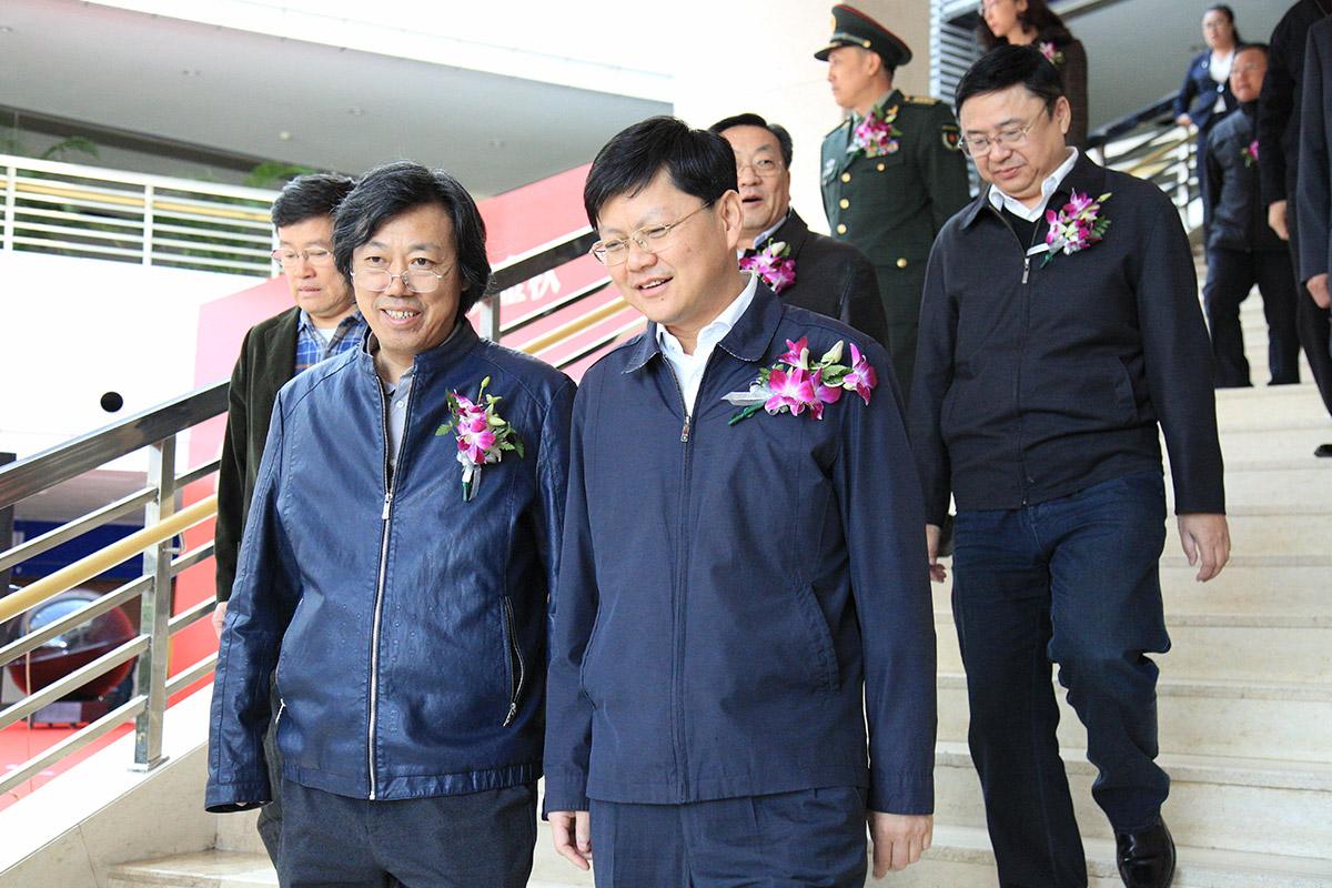 中国美术家协会艺术中心主任丁杰与营口市政府市长余恭斌正在进入画展开幕式现场